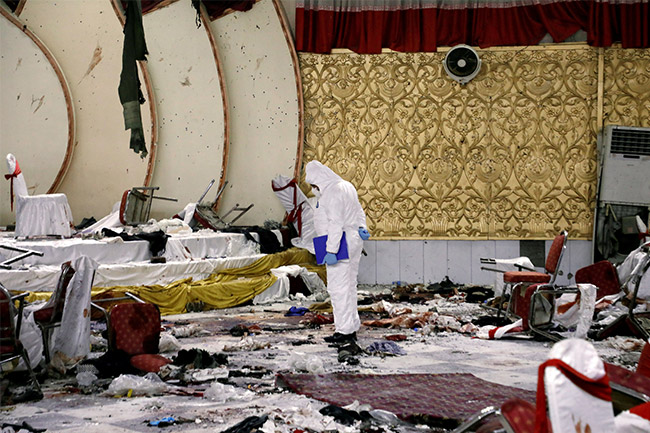 Seorang anggota pasukan keamanan Afghanistan menyelidiki di lokasi serangan bom bunuh diri kemarin di Kabul, Afghanistan.
