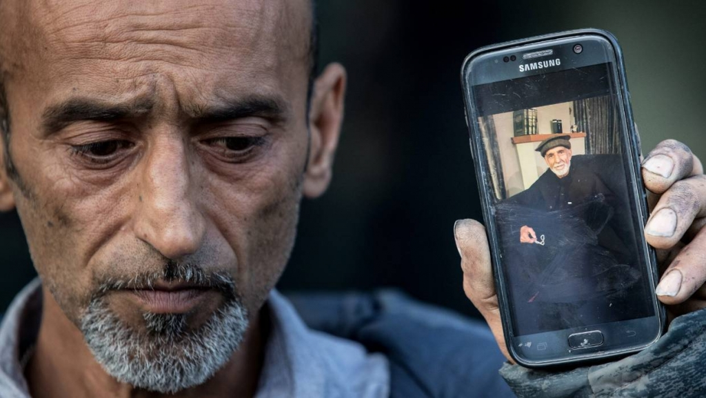Omar Nabi holds a photo of his father, 71-year-old Haji-Daoud
